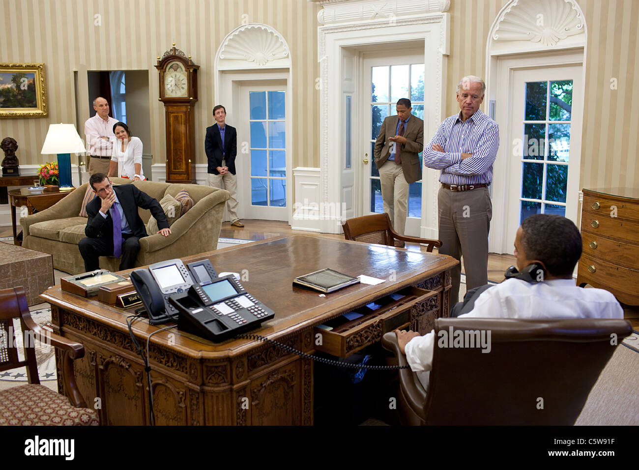 President Barack Obama talks on the phone with House Minority Leader Nancy Pelosi in the Oval Office to discuss - Stock Image