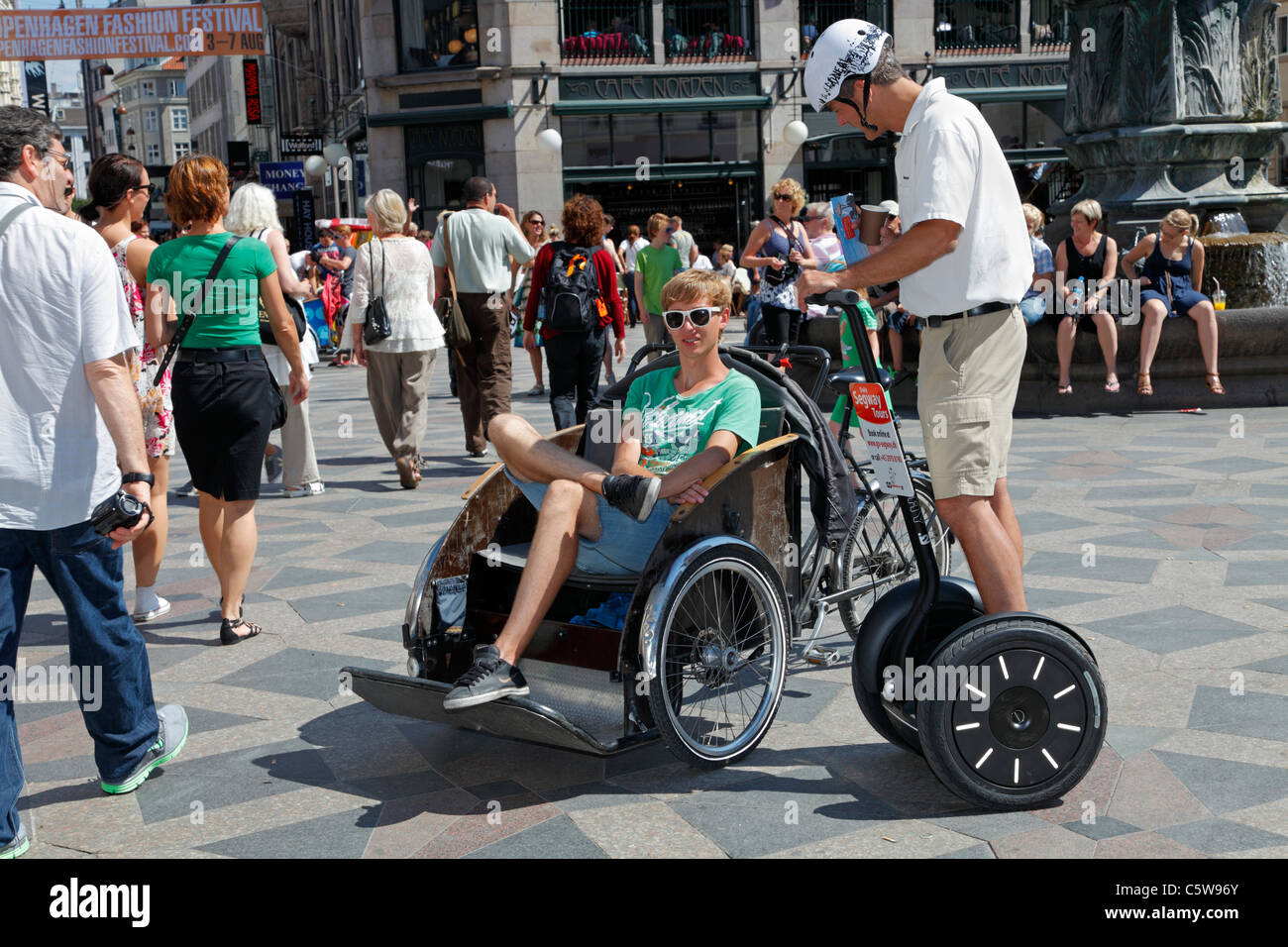 Idle bicycle taxi driver and Segway Tour guide relaxing among tourists on Strøget in Copenhagen on a warm and - Stock Image