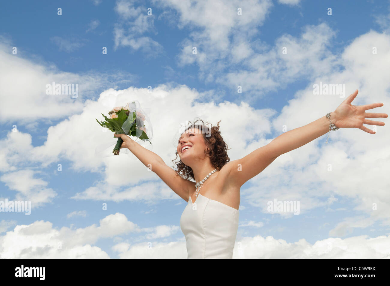 Germany, Bavaria, Smiling Bride with bouquet and arms outstreched , outdoors - Stock Image