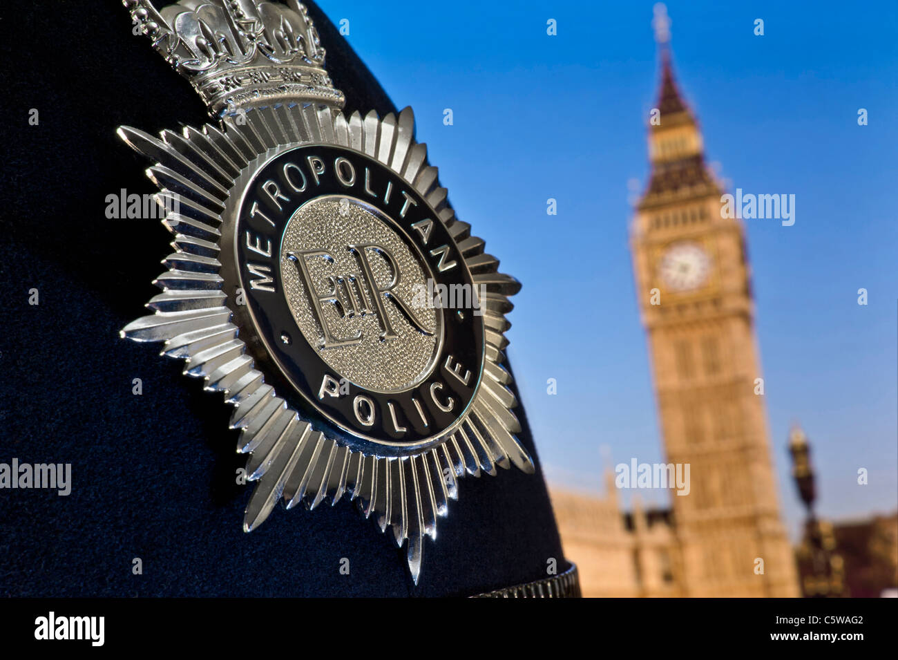 Close view on Metropolitan police helmet  and badge Houses of Parliament and River Thames Westminster London UK - Stock Image
