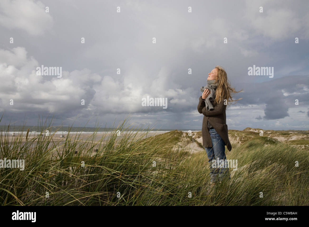 Germany, Schleswig Holstein, Amrum, Young woman on grassy sand dune - Stock Image