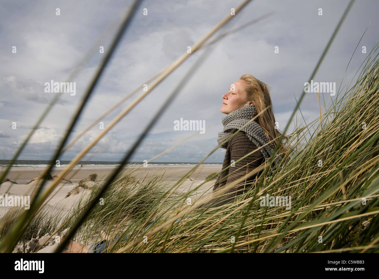 Germany, Schleswig Holstein, Amrum, Young woman on grassy sand dune, eyes closed Stock Photo