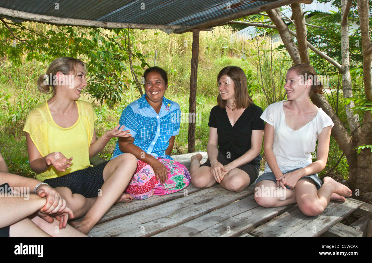 Volunteers visit with their hostess during a home stay at Ben Lion on KOH PHRA THONG ISLAND - THAILAND - Stock Image