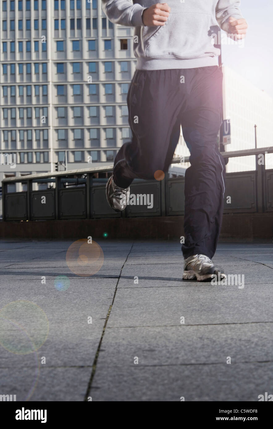 Germany, Berlin, Person jogging on street, skyscrapers in background, low section - Stock Image