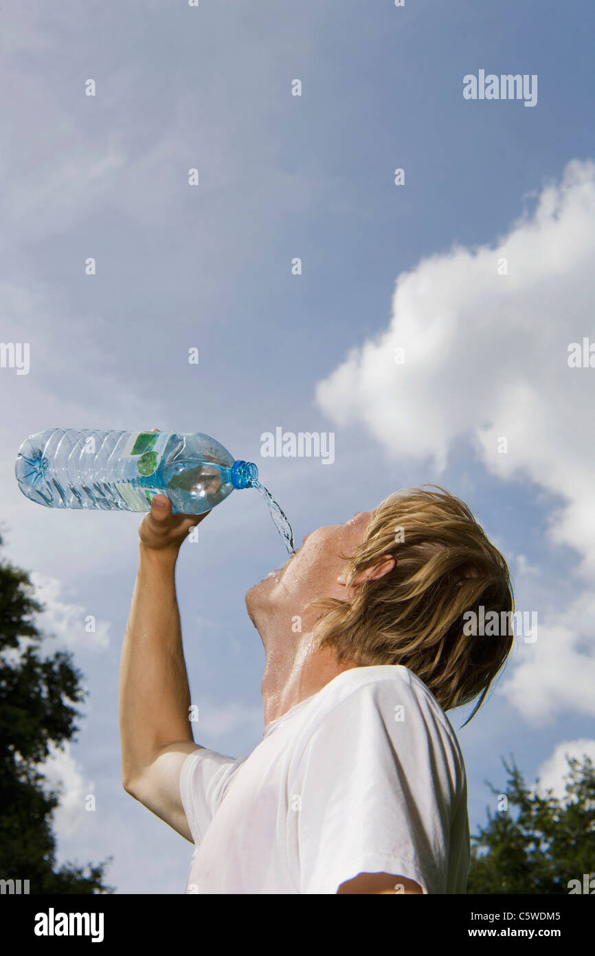 Germany, Berlin, Young man drinking from water bottle, portrait - Stock Image