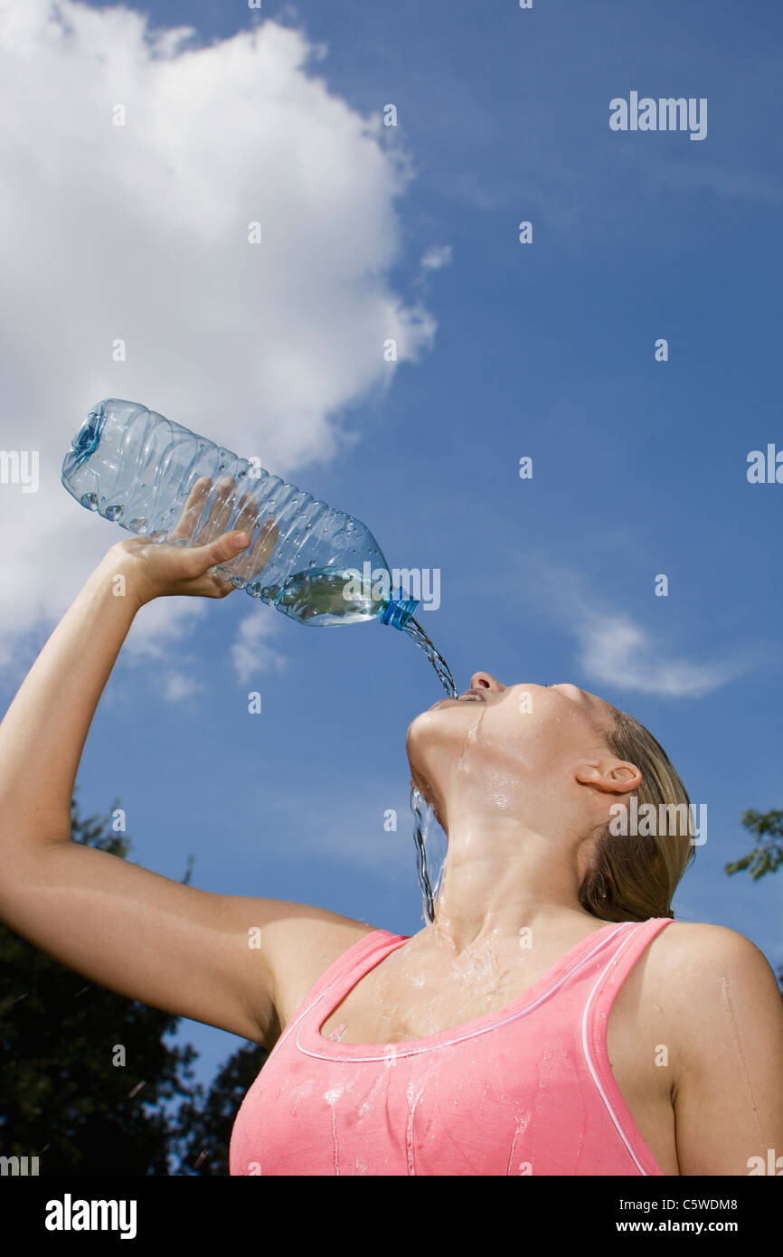Germany, Berlin, Young woman pouring water over face, portrait Stock Photo