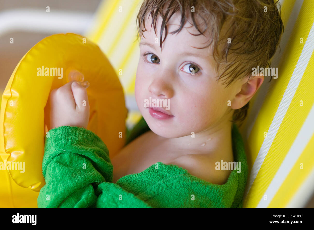 Germany, Baden-Württemberg, Boy (4-5) sitting on chair in indoor swimming pool, portrait - Stock Image