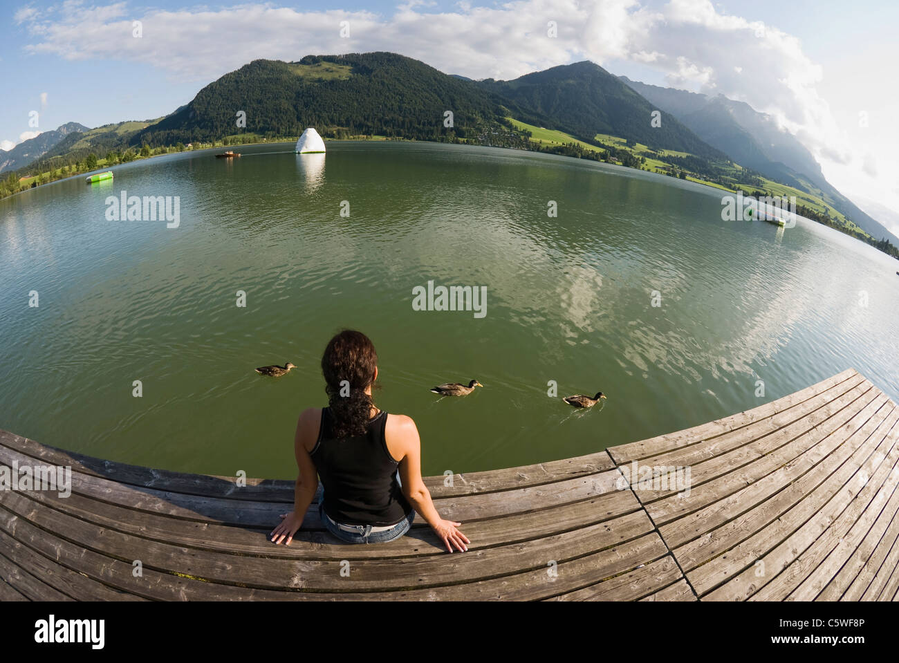 Austria, Tyrol, Walchsee, Woman relaxing on the waterfront, rear view, (fisheye) - Stock Image