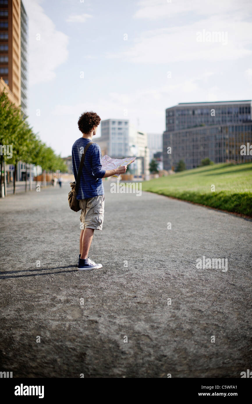 Germany, Berlin, Young man holding city map - Stock Image