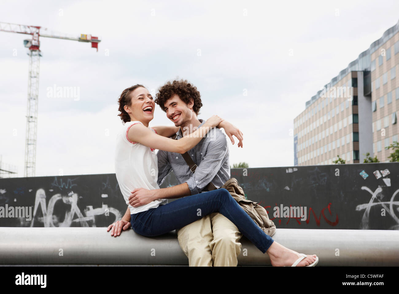 Germany, Berlin, Young couple in front of new building, cranes in background - Stock Image