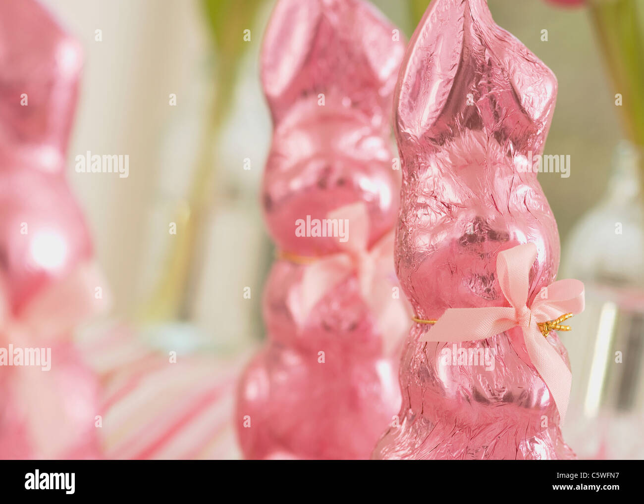 Pink wrapped chocolate easter bunnies - Stock Image