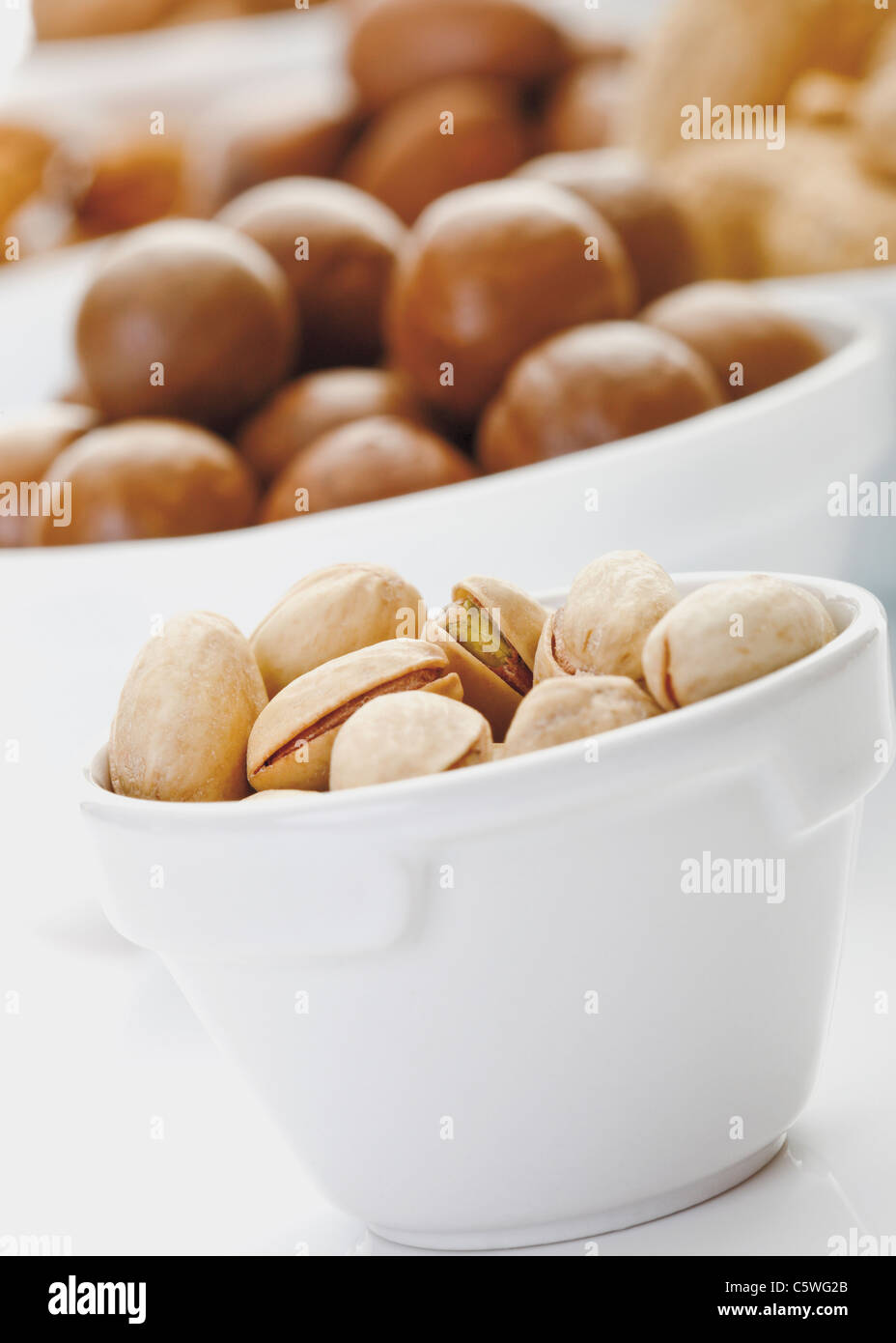 Pistachios and other nuts in bowls - Stock Image