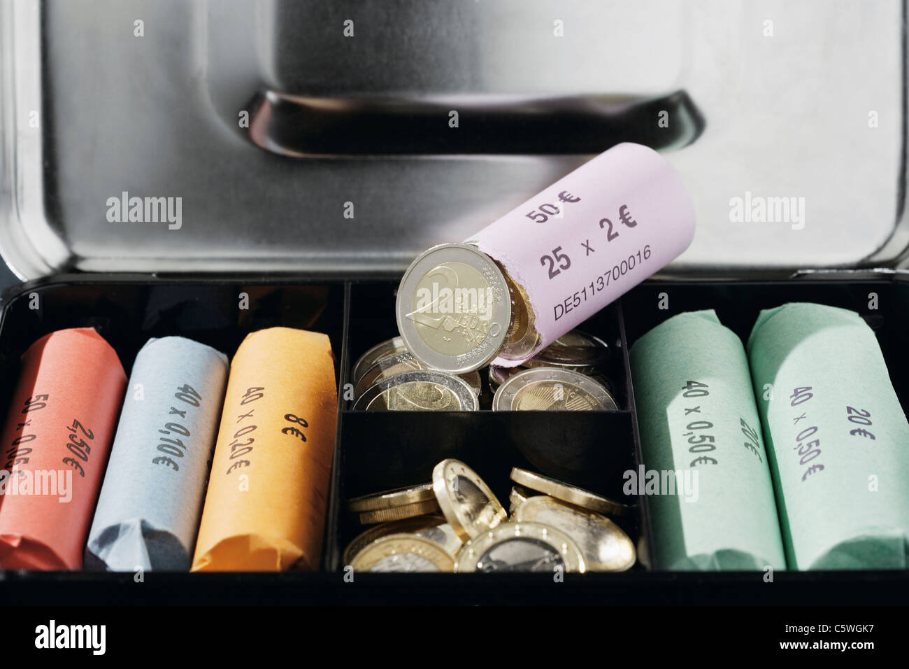 Close up of cash box with coin rolls - Stock Image