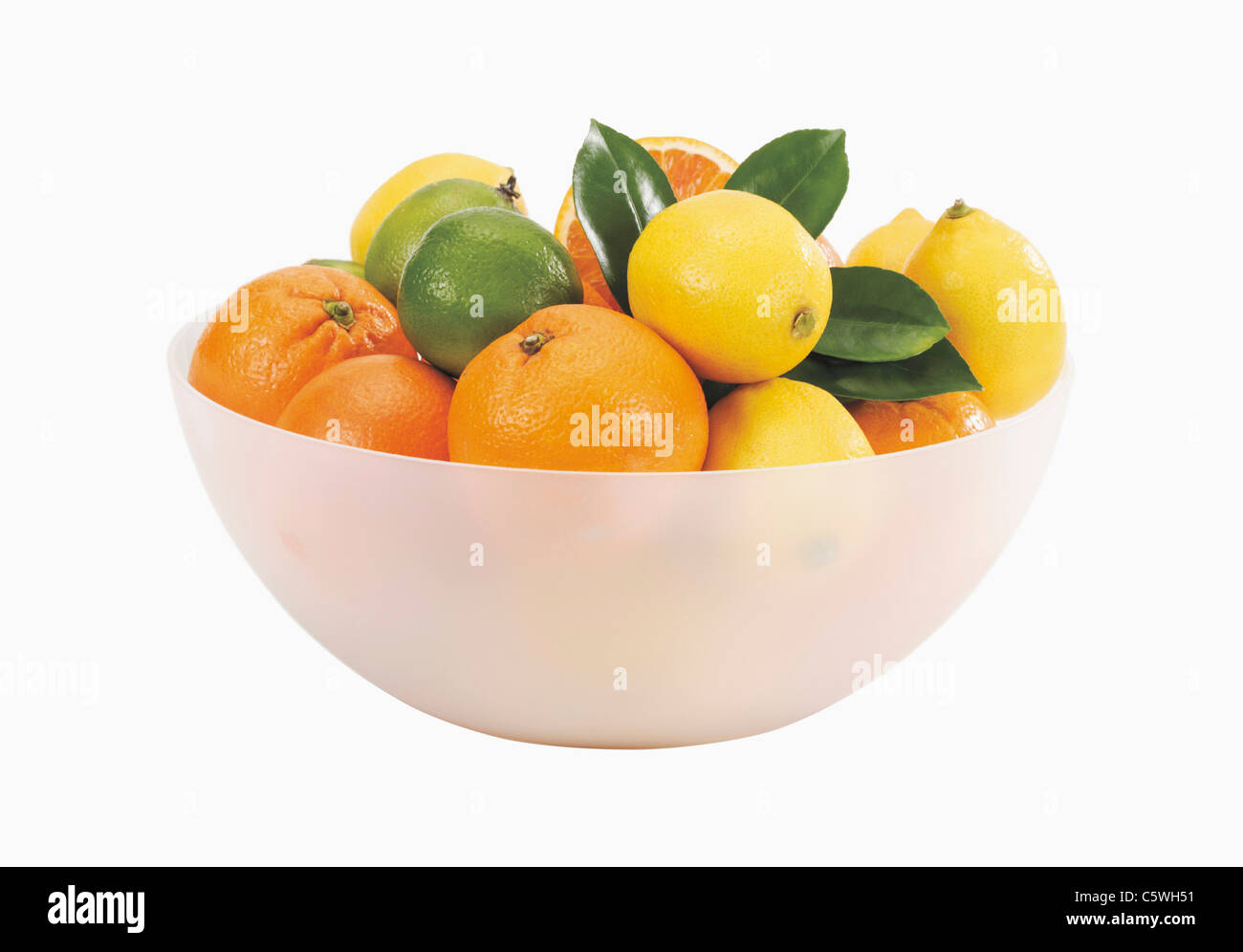 Bowl with fresh oranges and lemons against white background - Stock Image