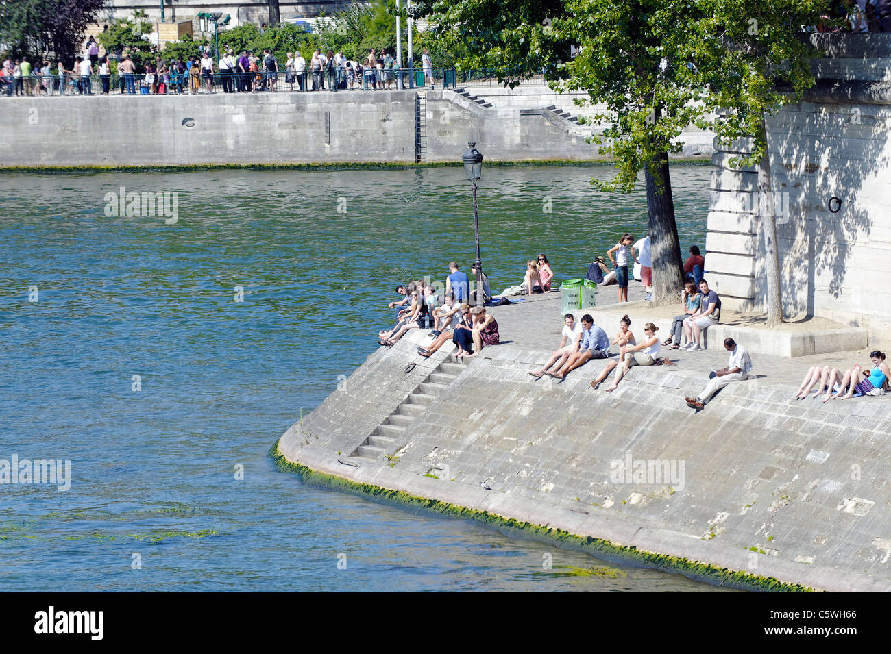 Parisians sunbathing on the banks of the River Seine - Stock Image