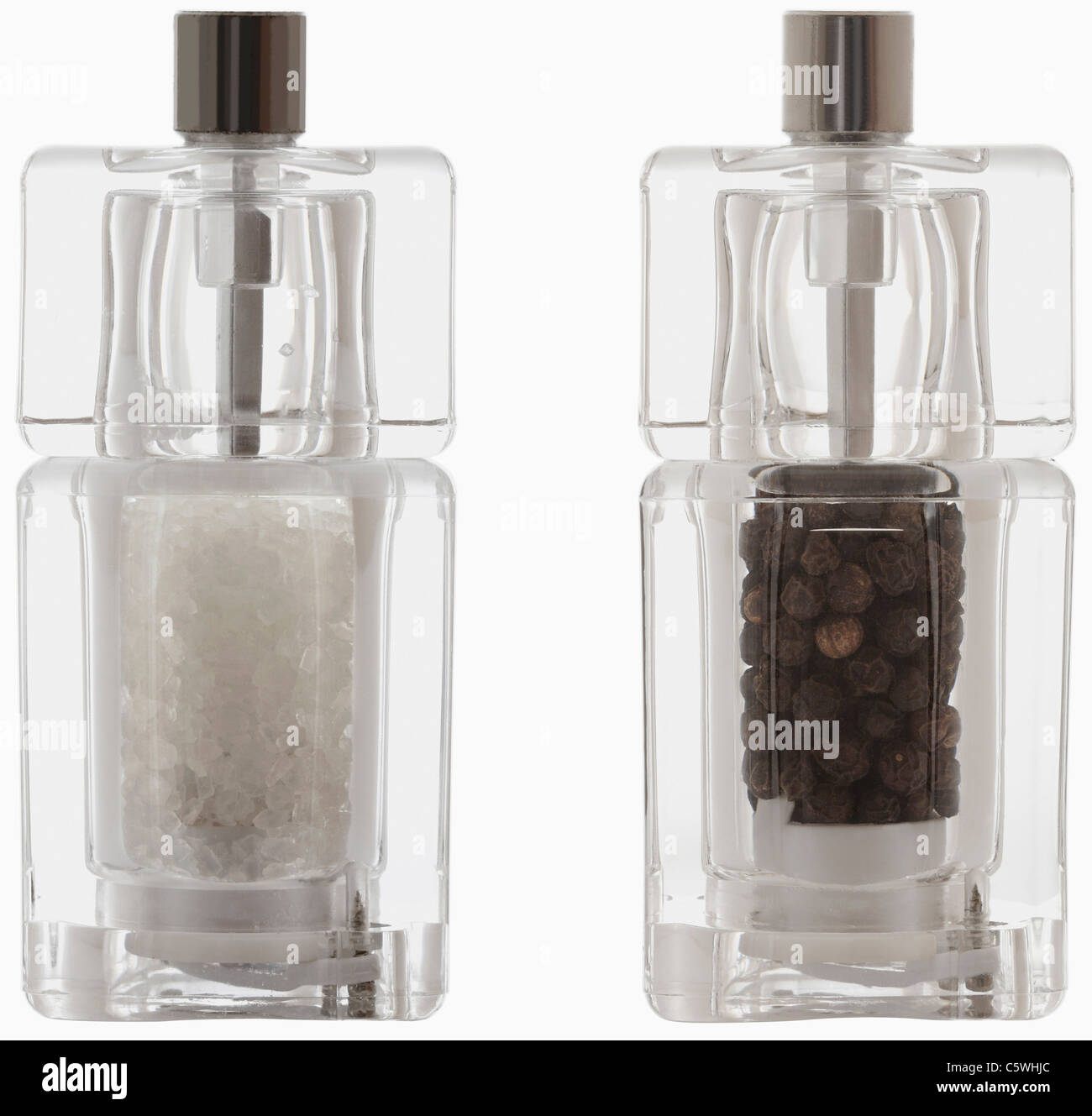 Salt and pepper mill of plexiglass against white background, close up - Stock Image