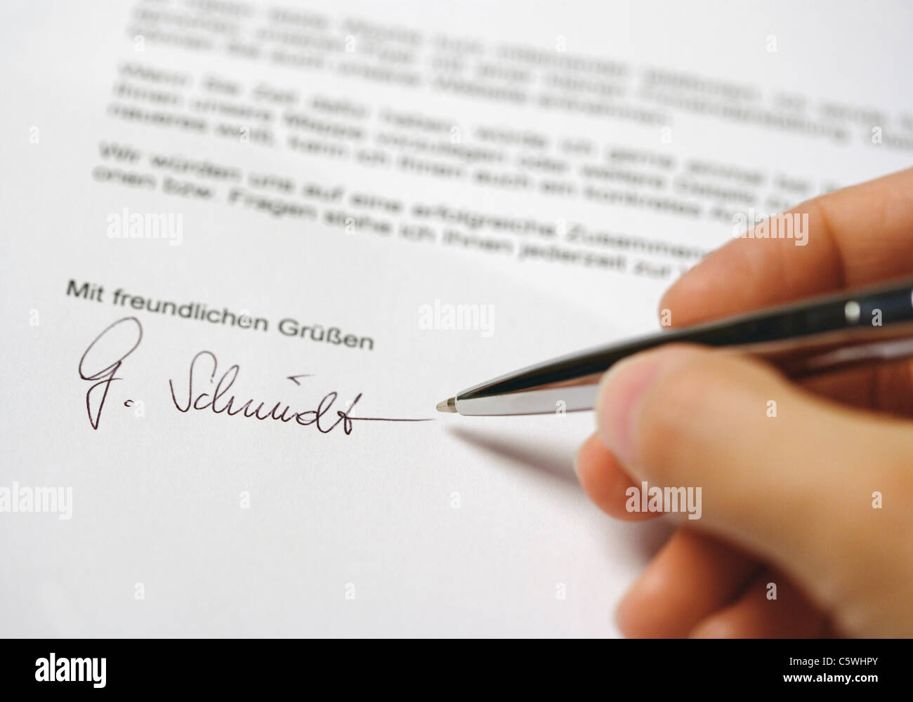 Close up of man hand signing letter - Stock Image