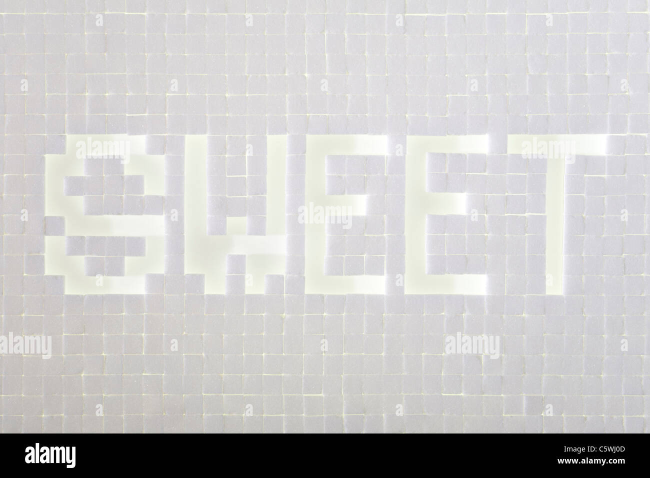 Sugar cubes forming the word sweet, elevated view - Stock Image