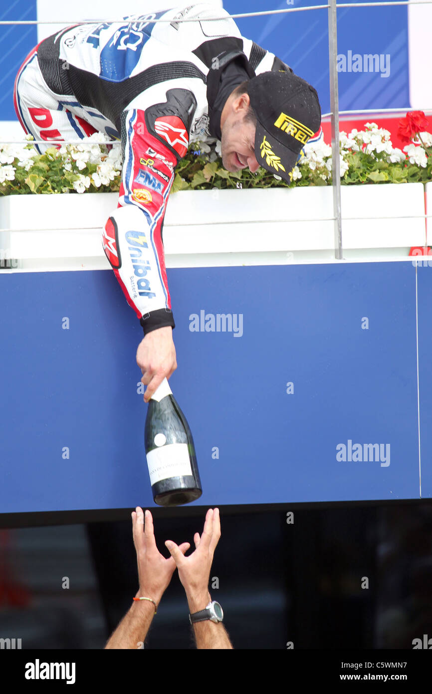 Race winner Carlos Checa passes the Champagne down to his mechanic Stock Photo