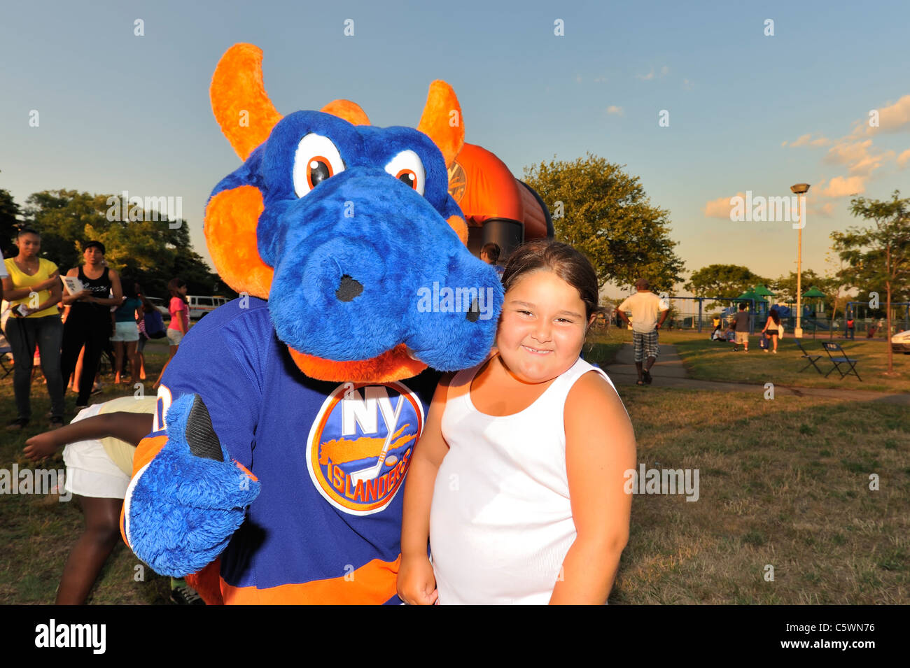 New York Islanders mascot, Sparky the Dragon, going 'thumb's up' with young girl, at National Night - Stock Image
