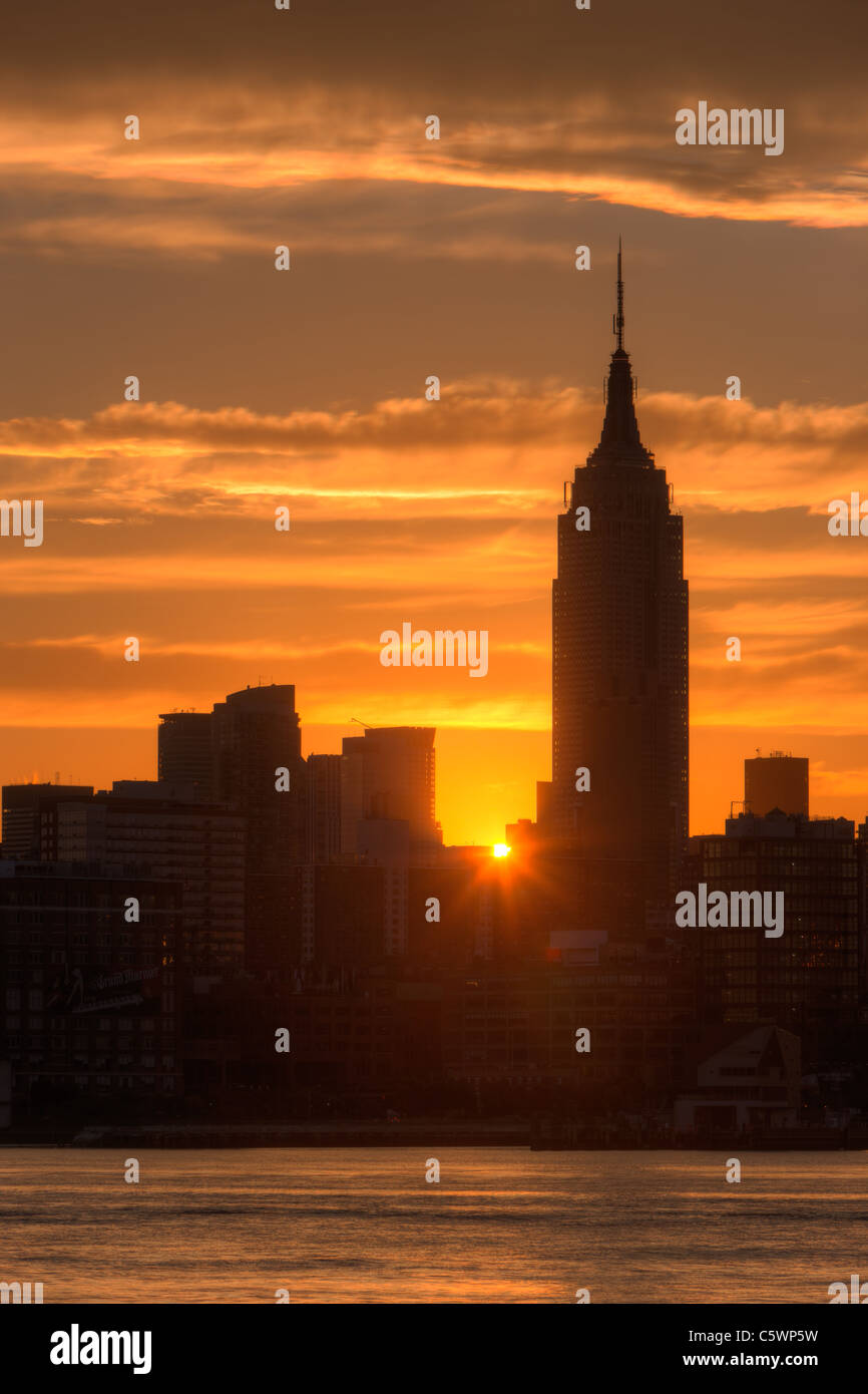The rising sun shines between Manhattan buildings including the Empire State Building just after sunrise in New - Stock Image