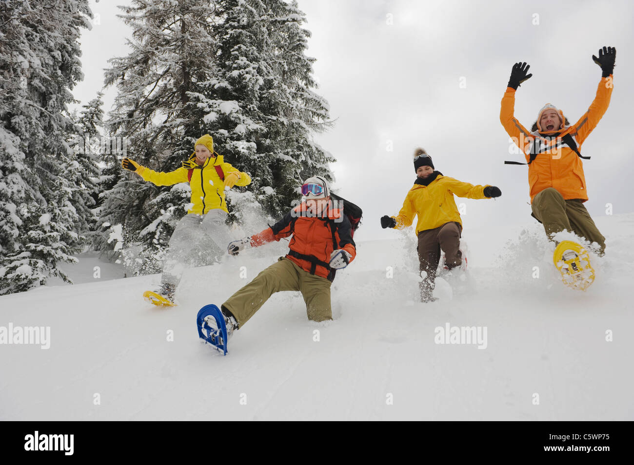 Italy, South Tyrol, People with snowshoes fooling about - Stock Image