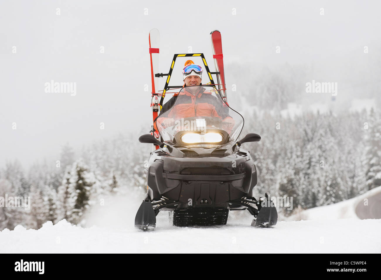 Italy, South Tyrol, Man driving snowmobile - Stock Image