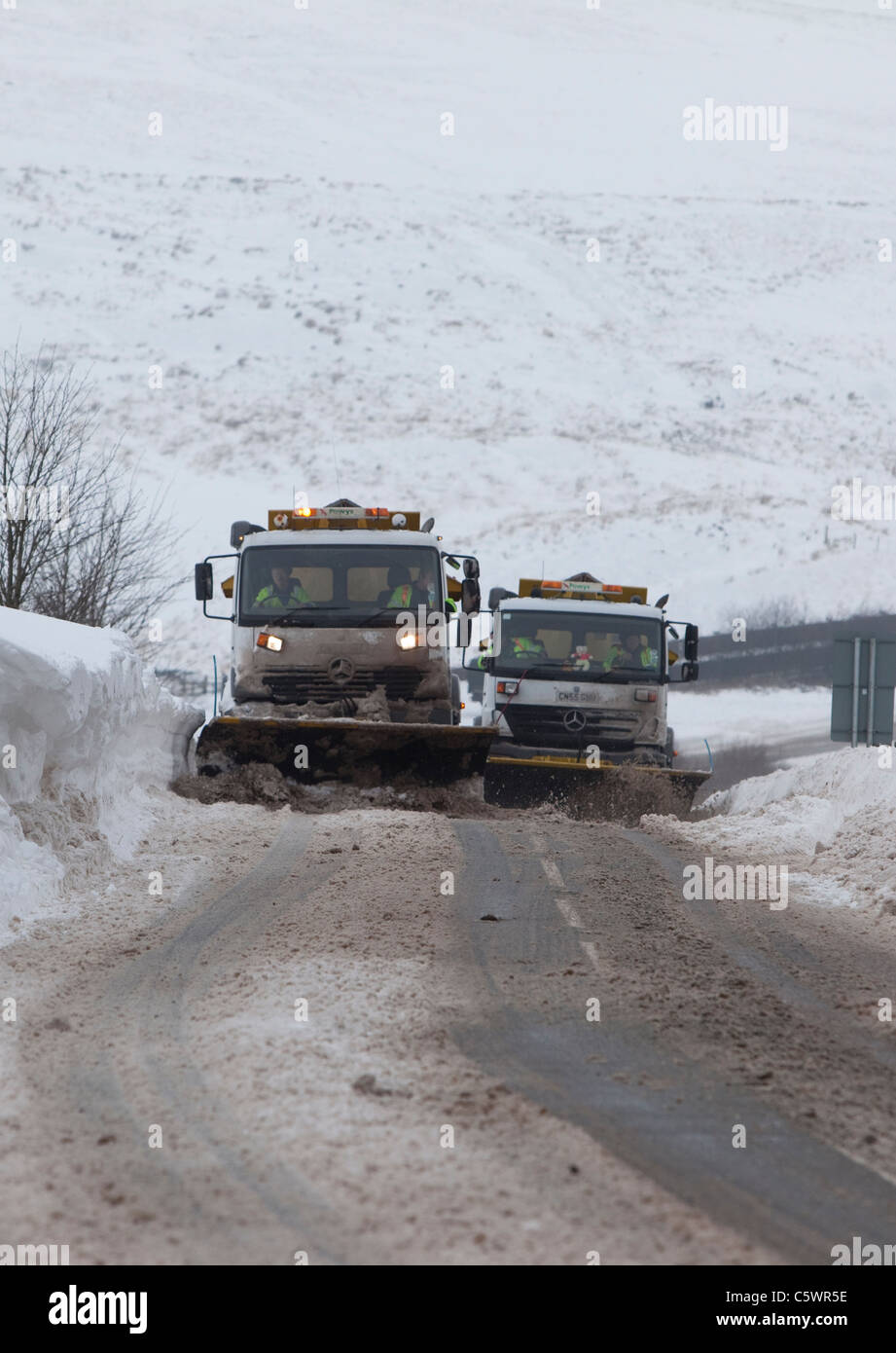 Council snow-ploughs and gritters work to clear the A4067 between Brecon and Swansea after heavy overnight snowfall. - Stock Image