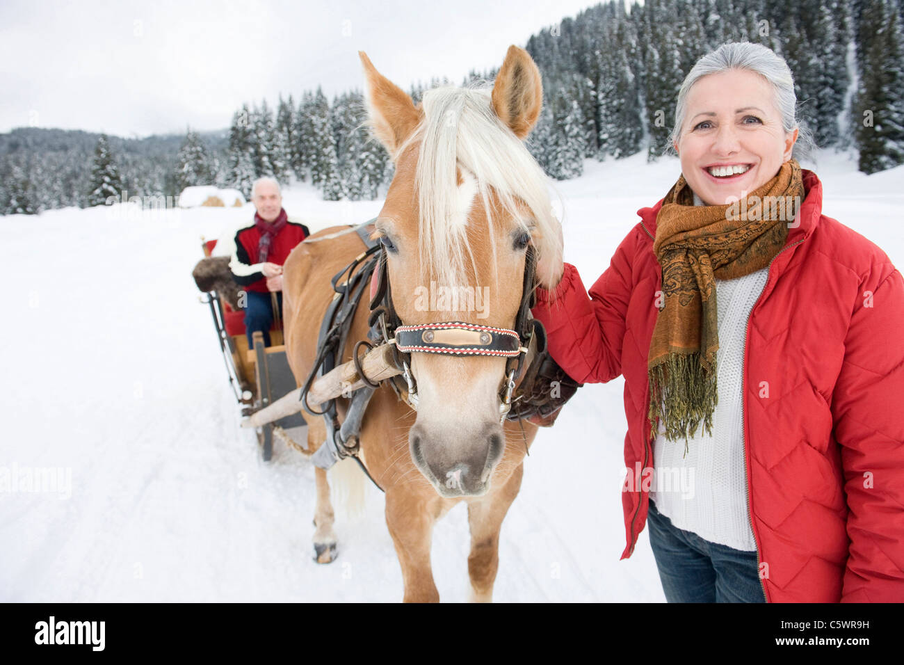 Italy, South Tyrol, Seiseralm, Senior woman standing by horse, man sitting in sleigh, smiling, portrait Stock Photo