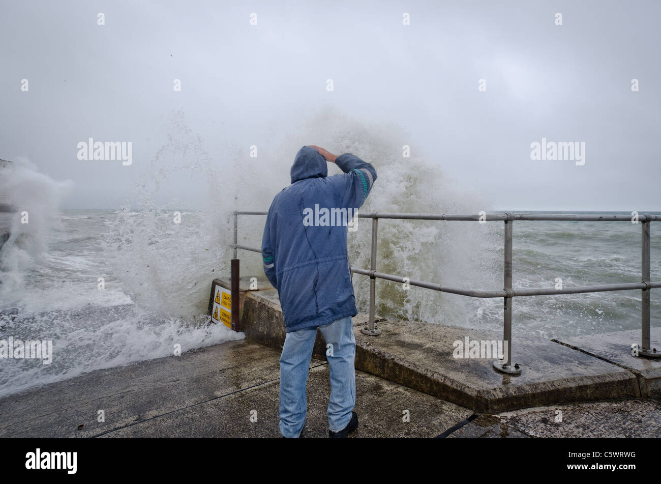 A man braves the stormy weather at Saltdean, ast East Sussex, promenade, as waves hit the breakwater. - Stock Image