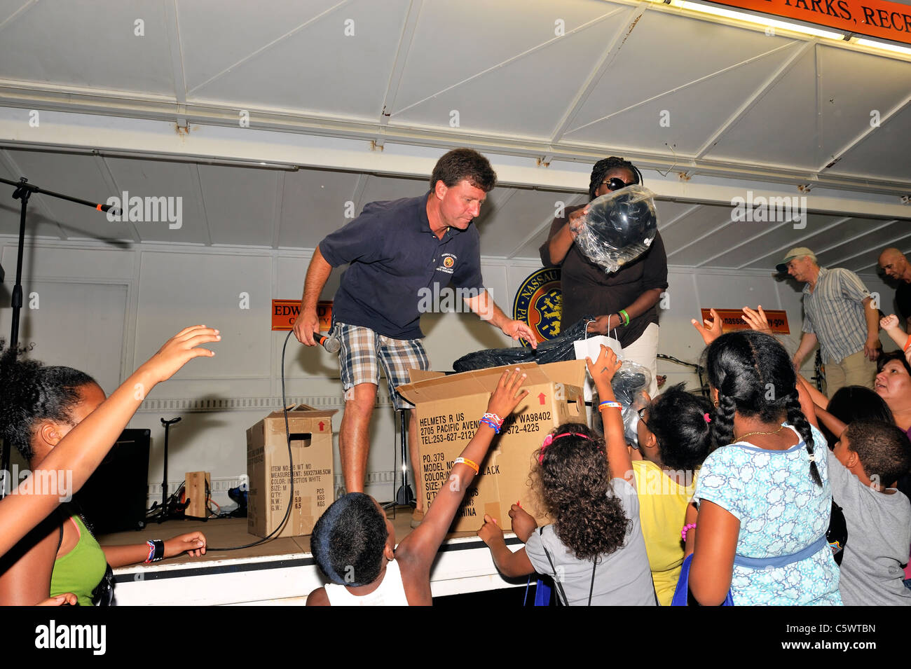 Legislator Dave Denenberg handing out 20 free bicycle helmets to children at National Night Out, at Freeport, NY, - Stock Image