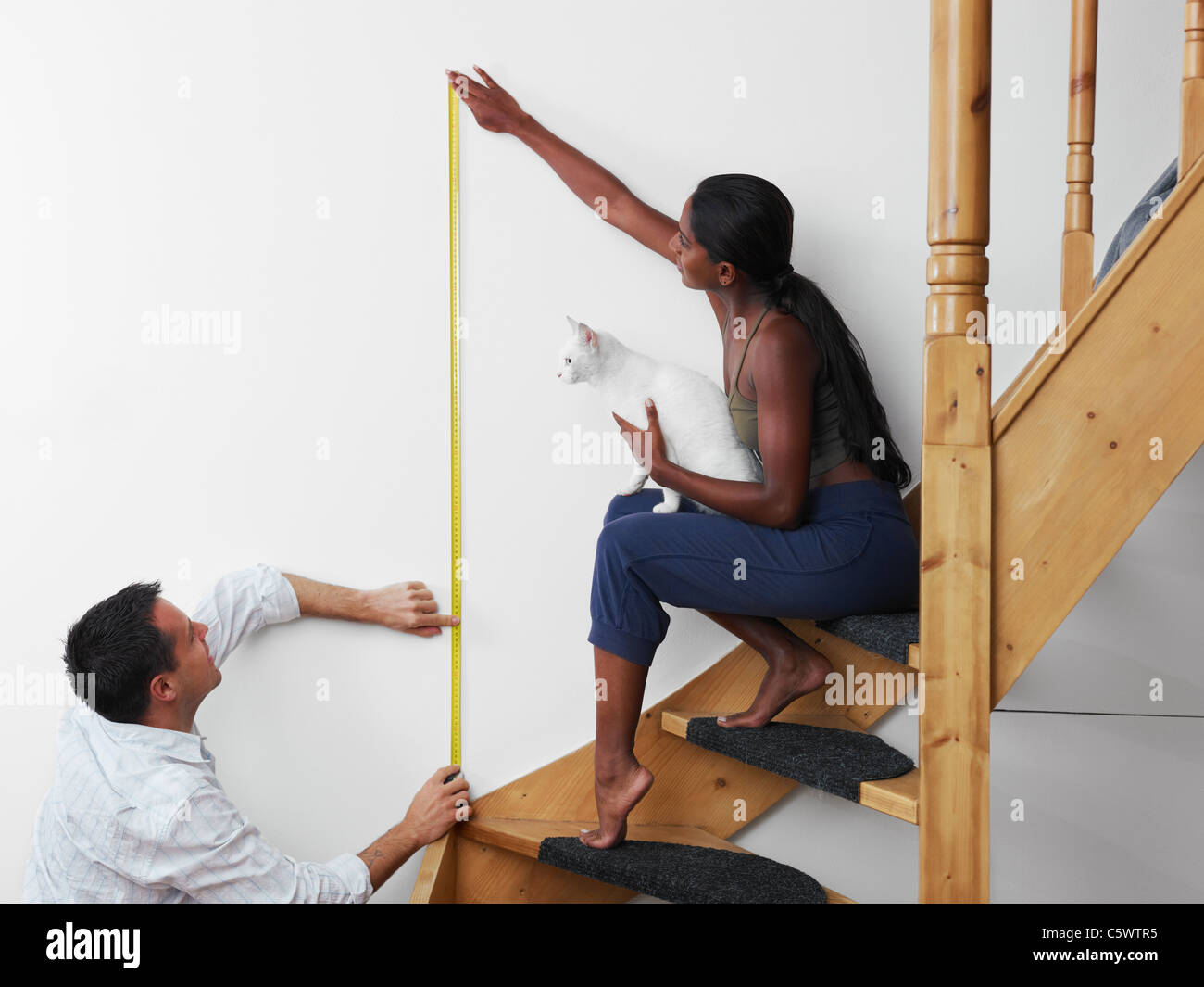 Do it yourself: couple measuring wall to hang picture at home. Horizontal shape, copy space - Stock Image
