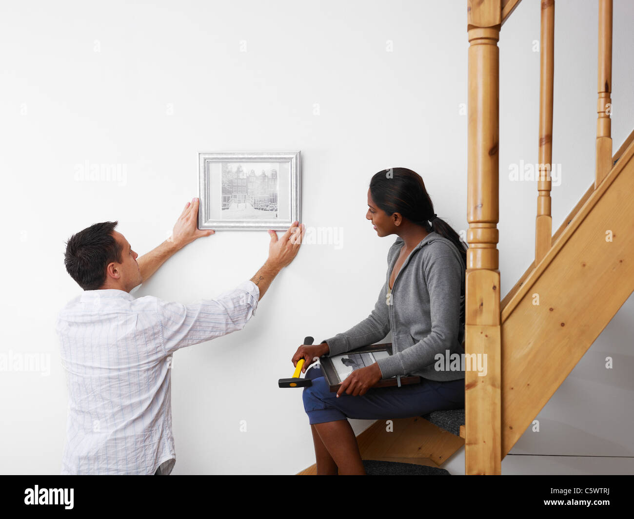 mid adult multiethnic couple hanging pictures to the wall and smiling. Horizontal shape, copy space - Stock Image
