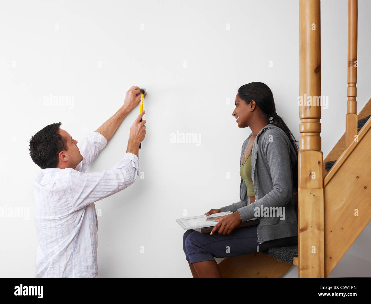 mid adult multiethnic couple using hammer to hang pictures to the wall and smiling. Copy space - Stock Image