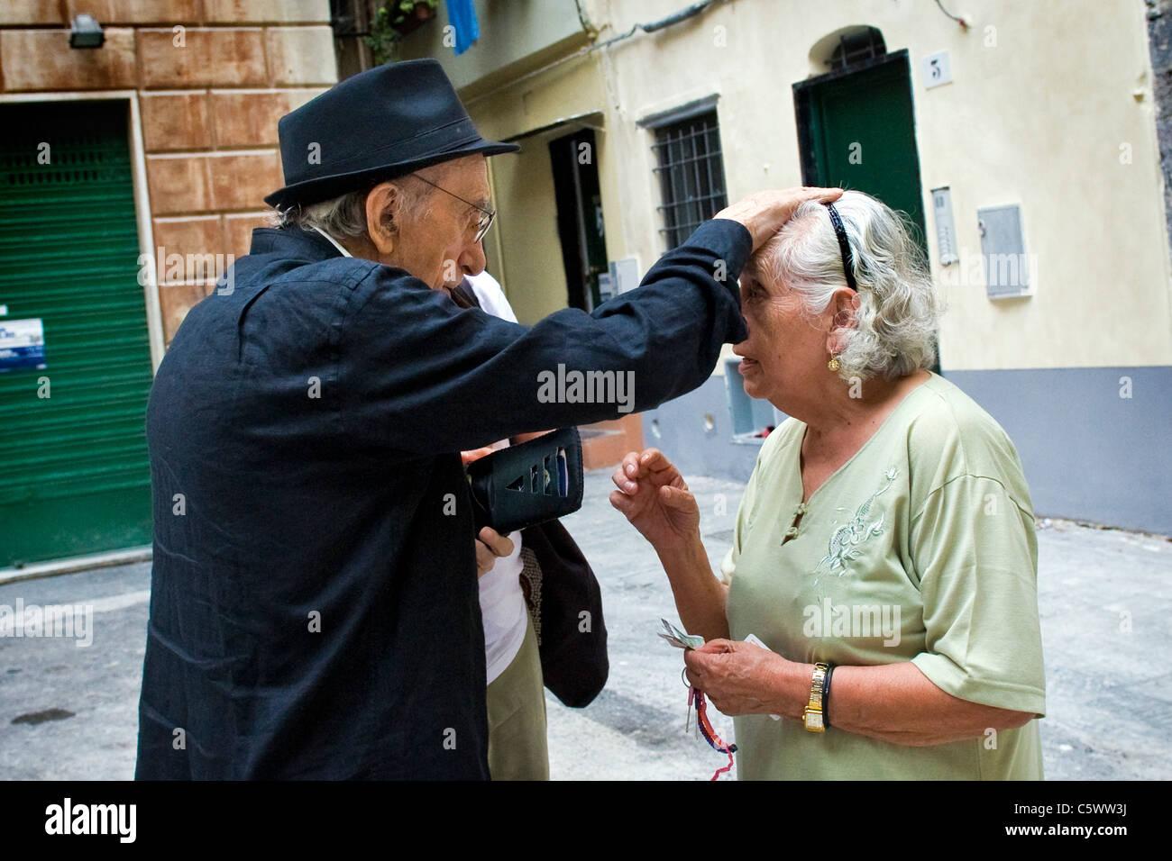 Don Andrea blesses a Peruvian woman. Don Andrea Gallo, Genoa, Italy - Stock Image