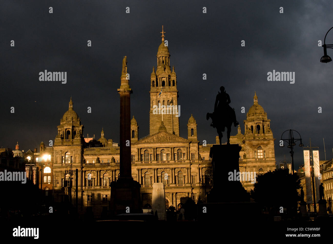 City Chambers, Glasgow's main public building is illuminated by strong evening sunlight, with a dark stormy - Stock Image