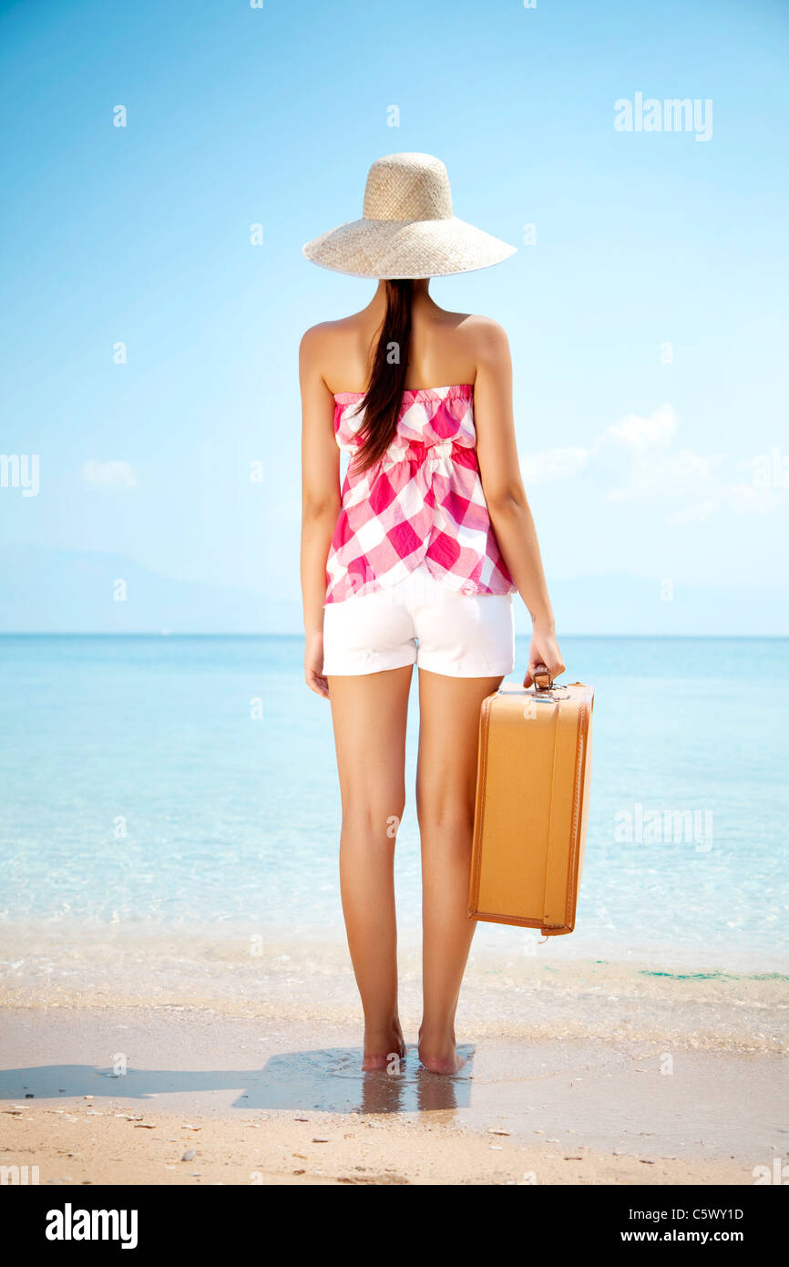 young female standing on the beach with vintage suitcase - Stock Image
