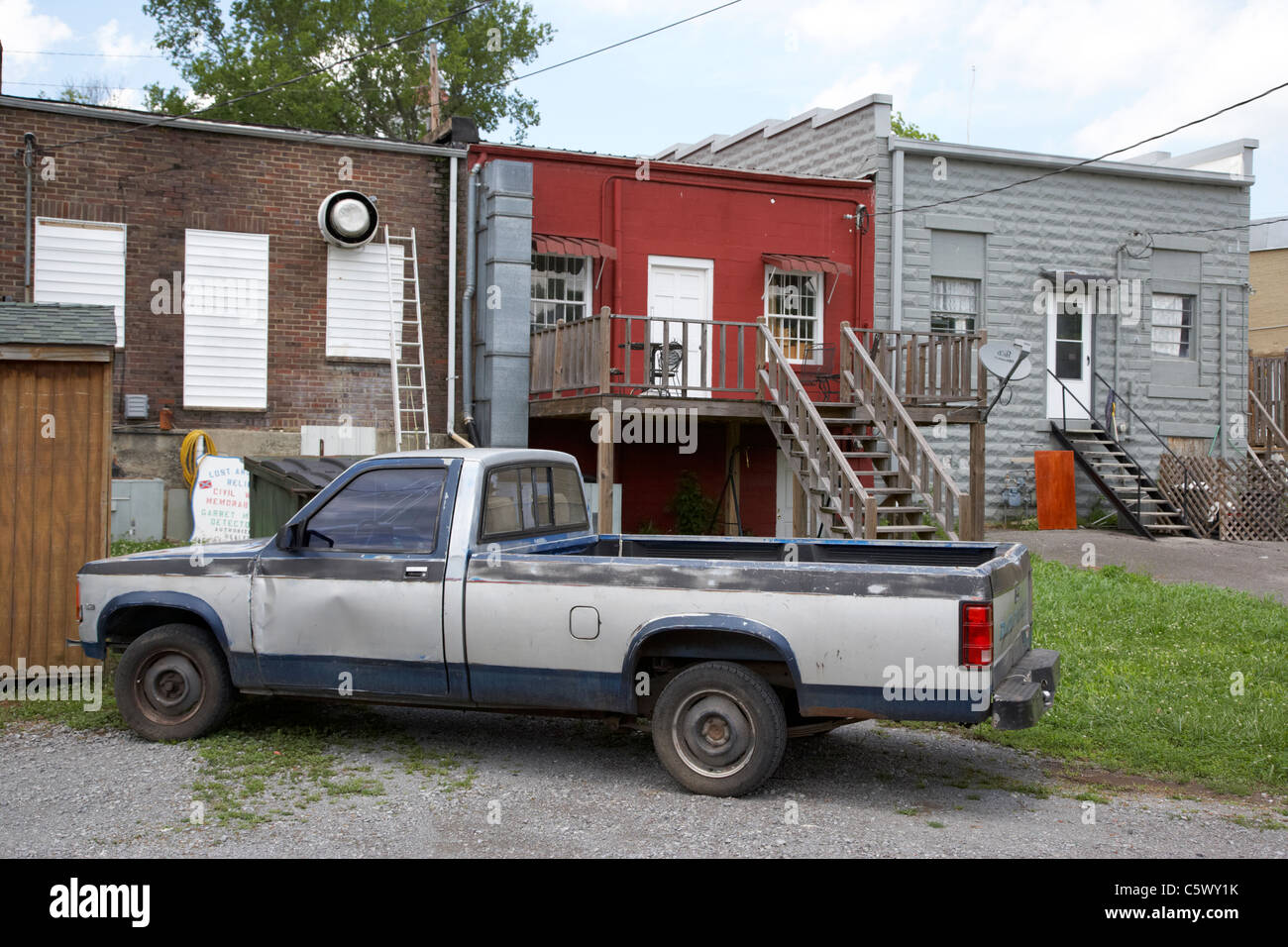 old pickup truck in parked at rear of shops and stores access main street Lynchburg , tennessee , usa - Stock Image