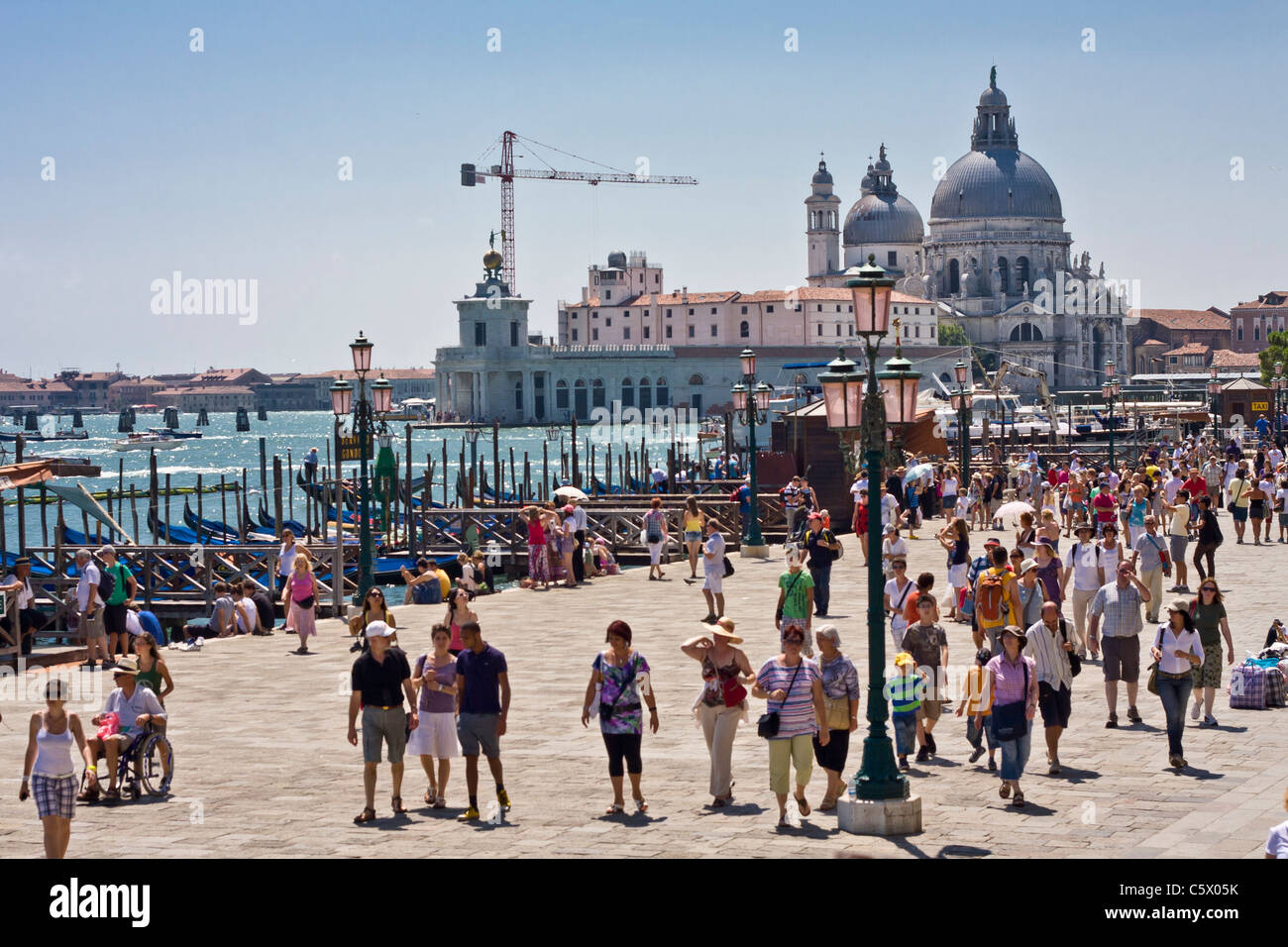 Tourists walking near Piazza San Marco on a bright sunny day in Venice Italy - Stock Image