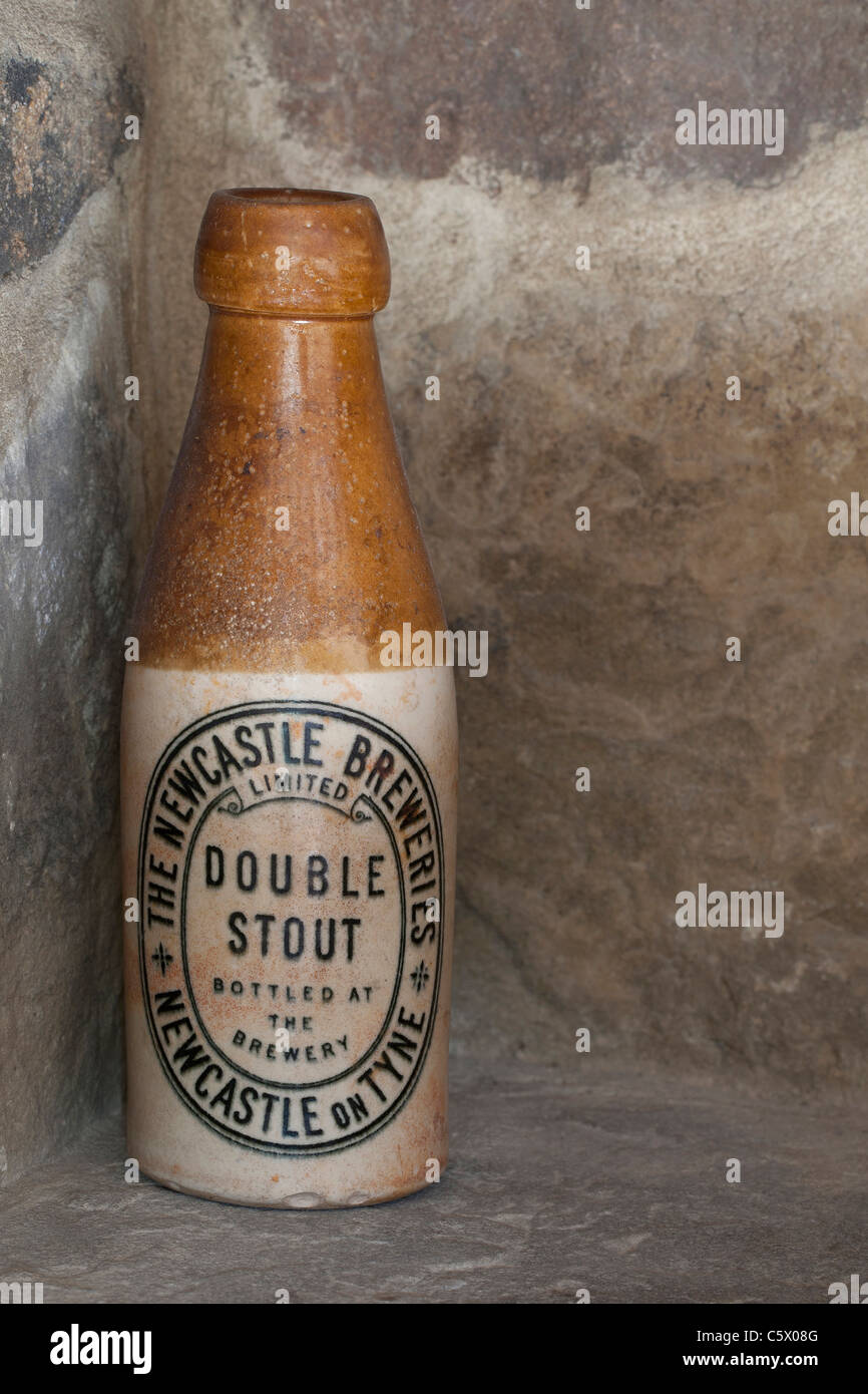 Antique Newcastle Breweries double stout brown ale ceramic bottle against a stone wall - Stock Image
