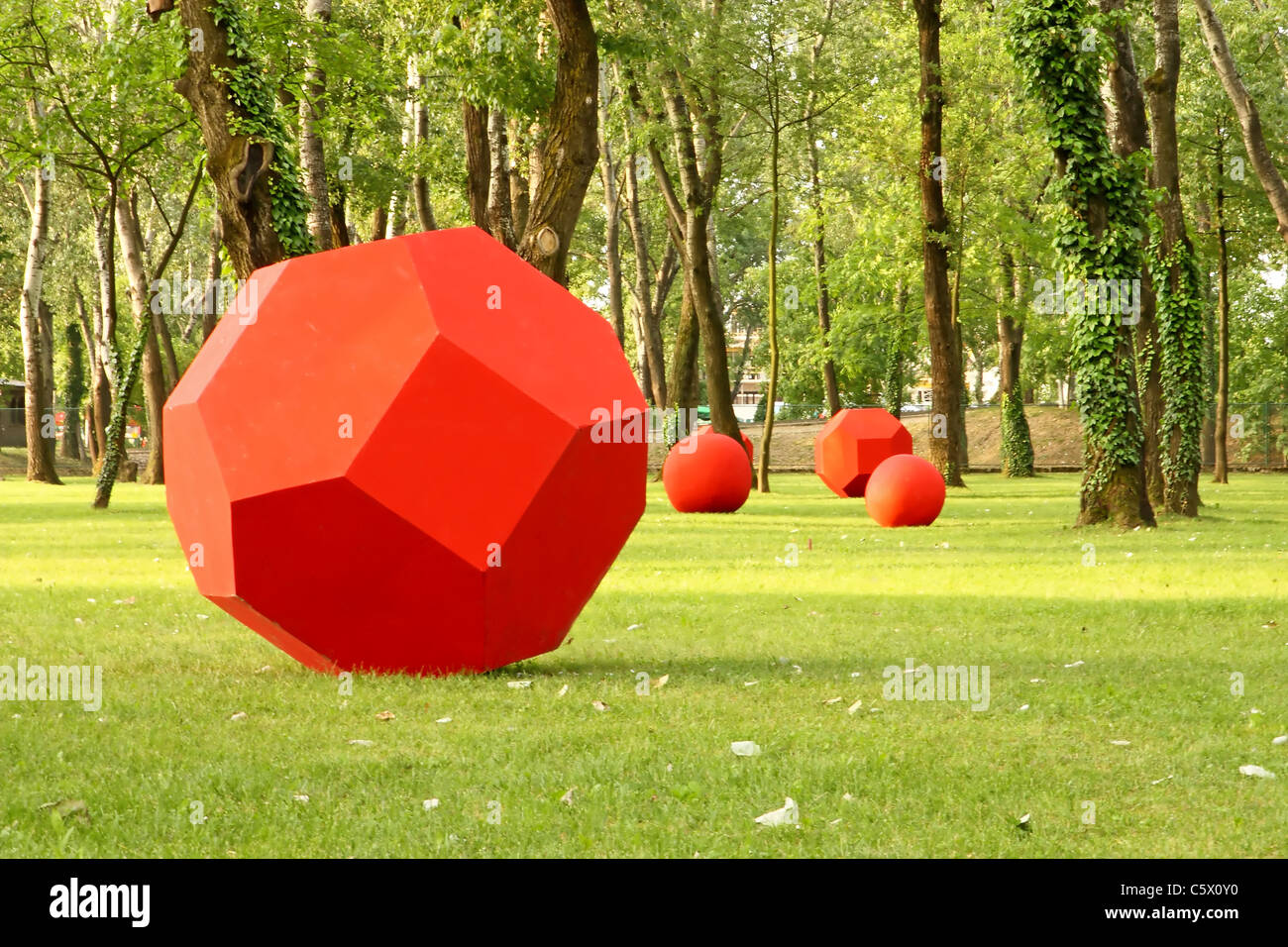 Red geometrical forms on green grass in wood - Stock Image