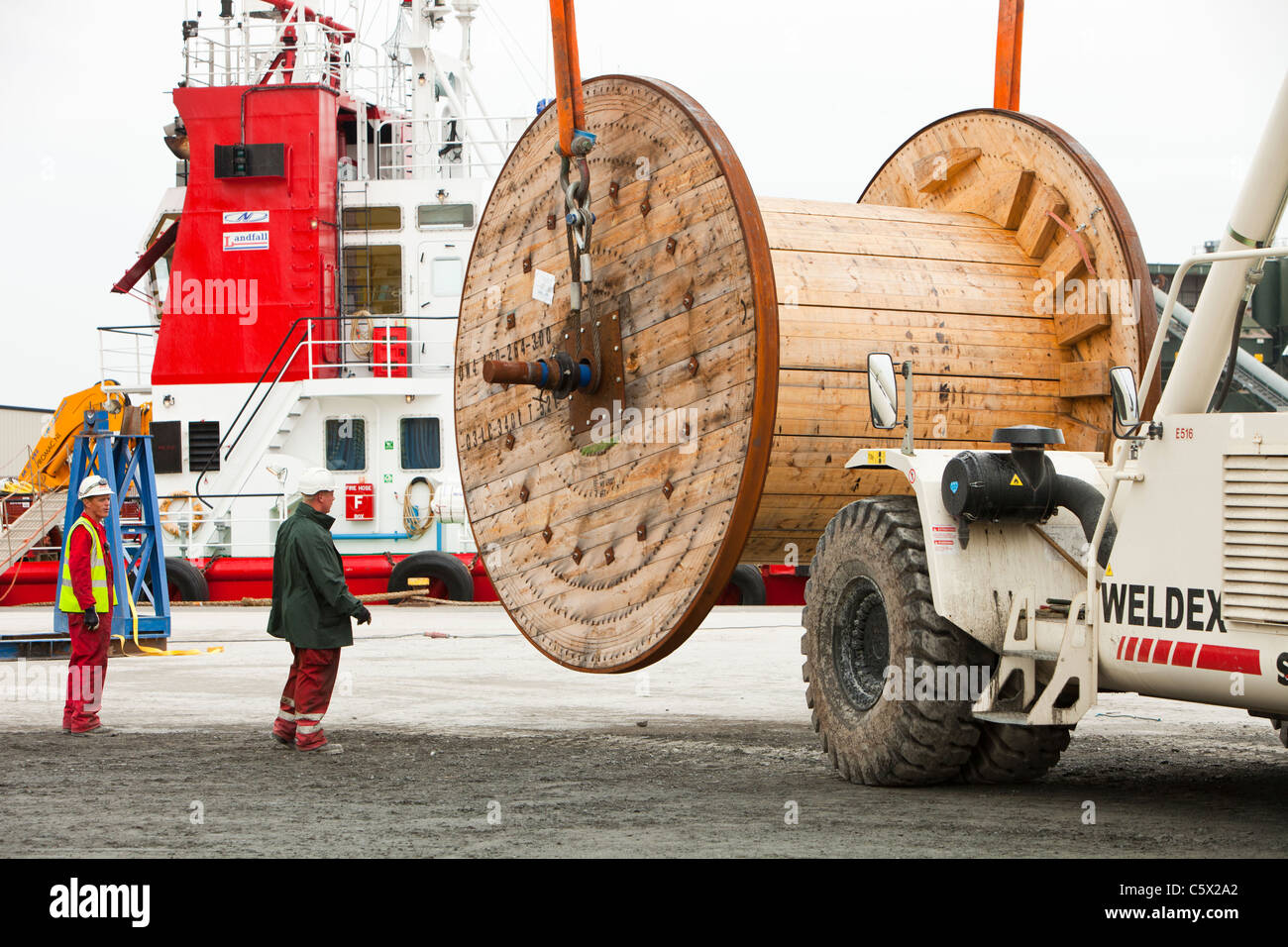 Offshore electric cabling for the Walney Offshore windfarm project being loaded onto a cable laying vessel in the - Stock Image