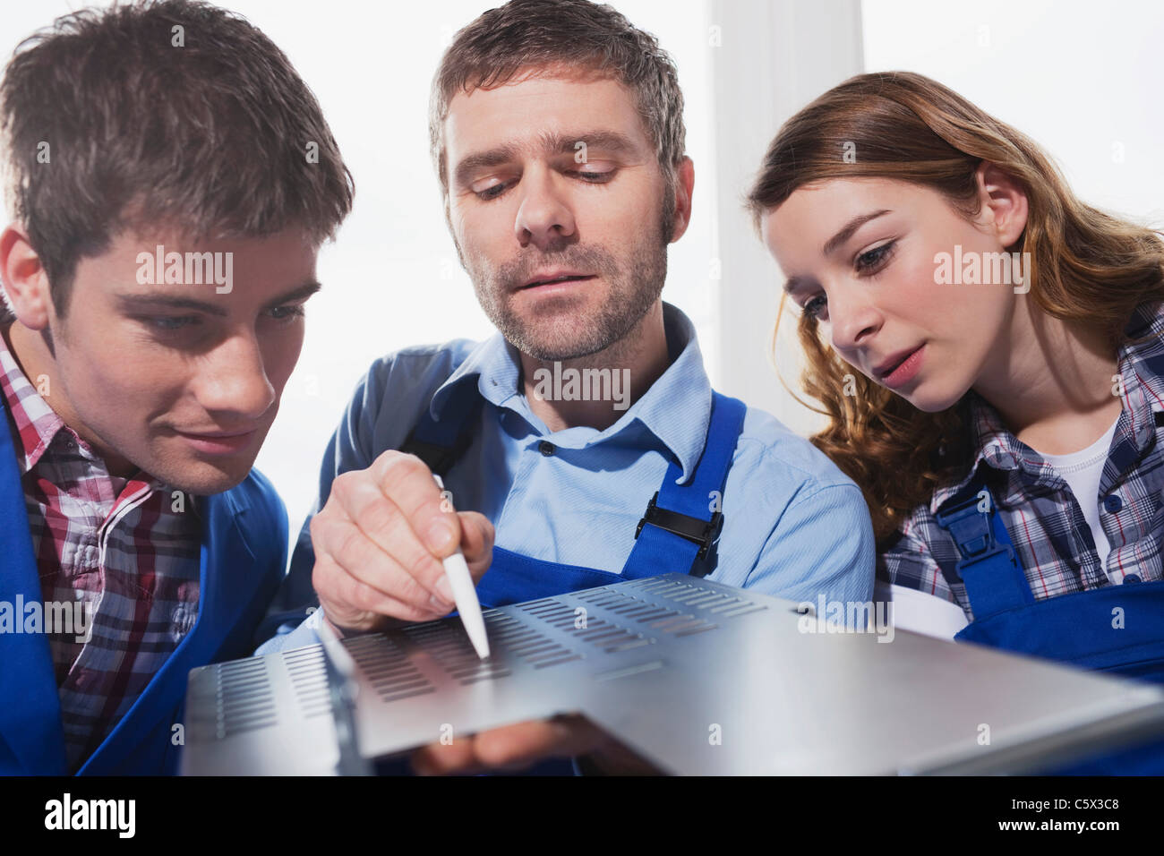 Germany, Neukirch, Apprentices and foreman, portrait - Stock Image