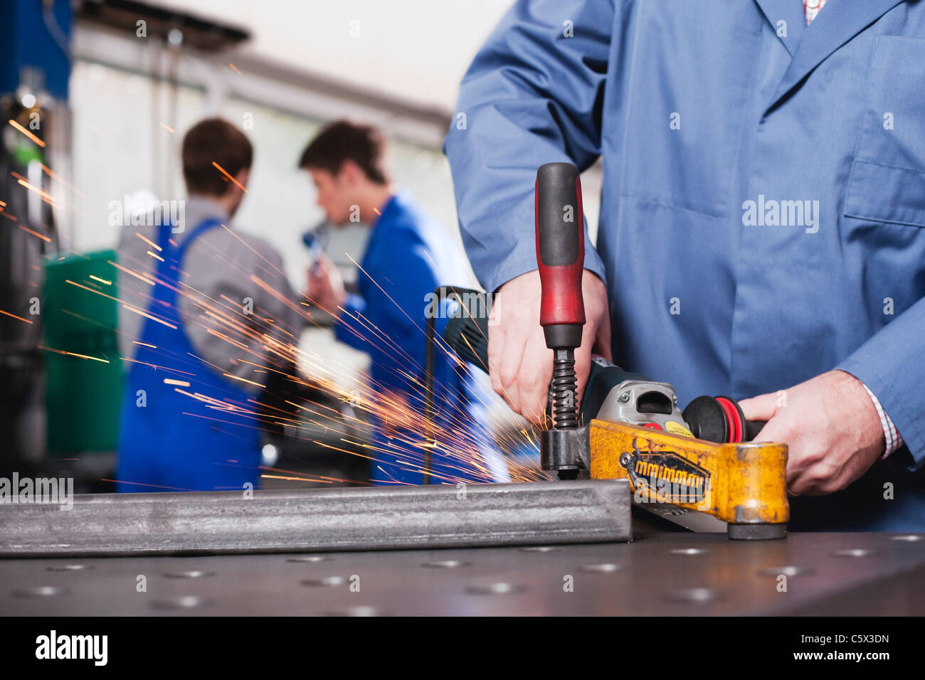 Germany, Neukirch, Person using grinder,  Apprentice and foreman in background Stock Photo