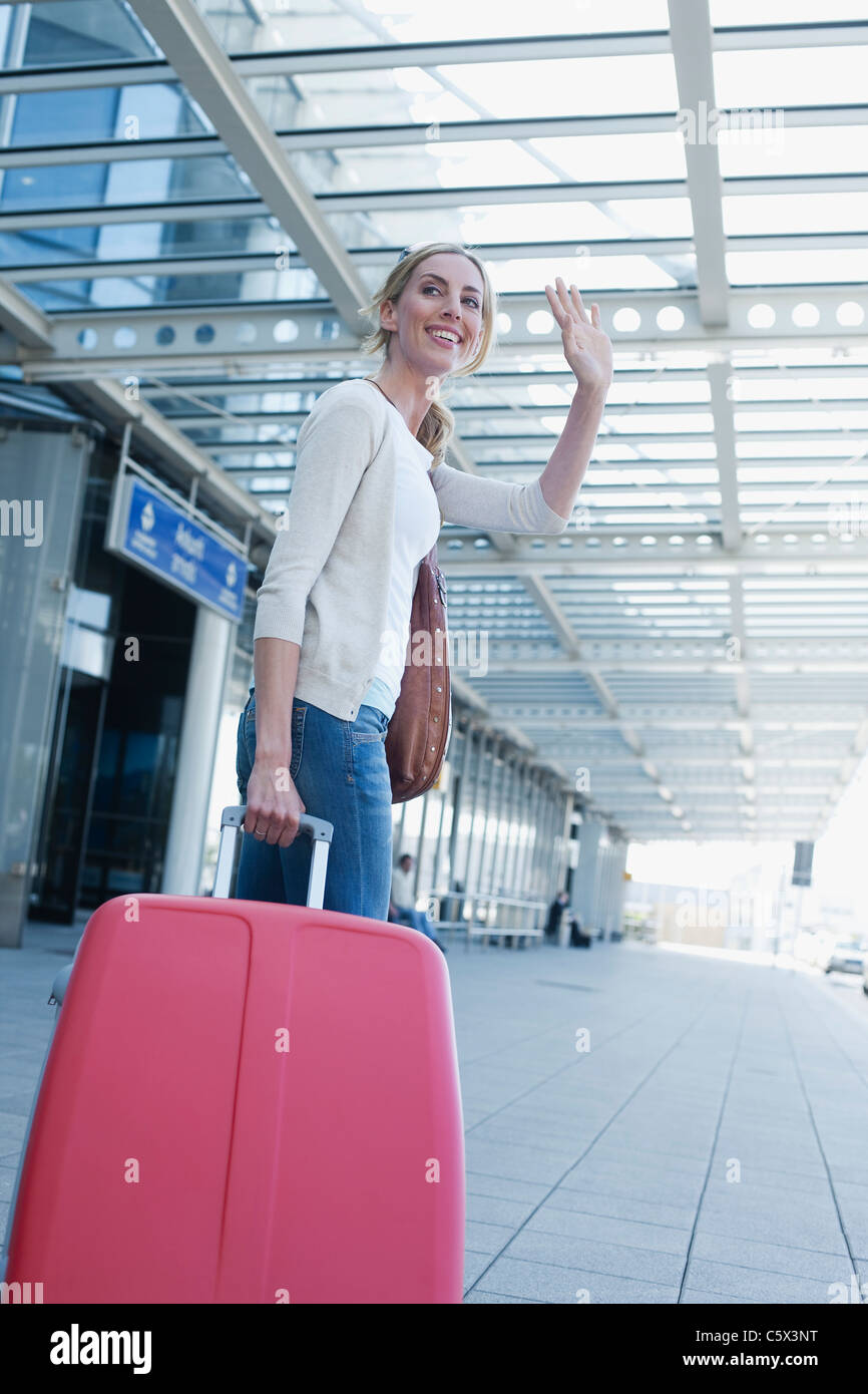 Germany, Leipzig-Halle, Airport, Young woman with suitcase, waving - Stock Image