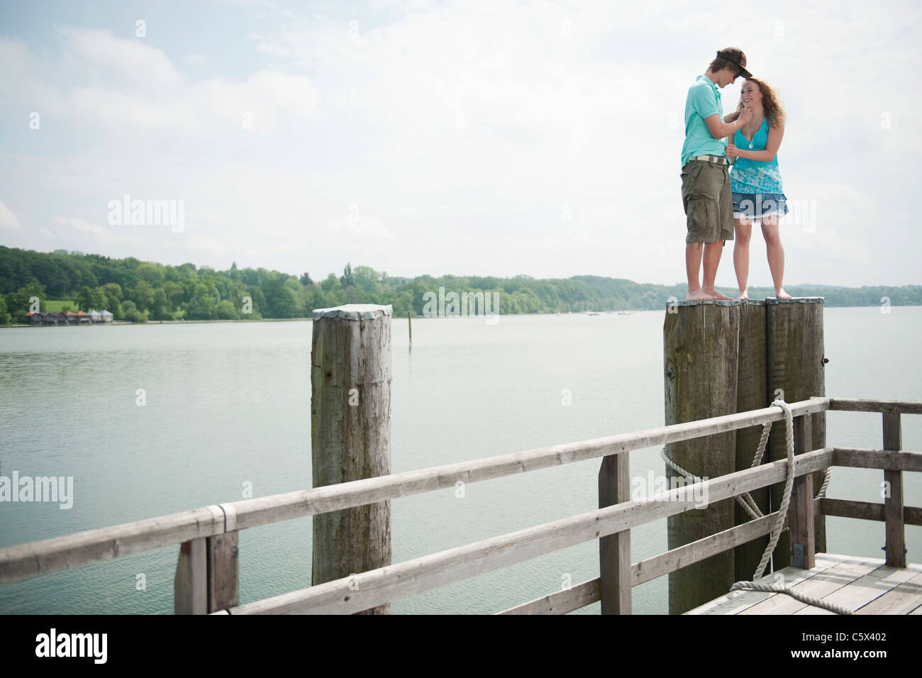 Germany, Bavaria, Ammersee, Young couple standing on wooden post - Stock Image