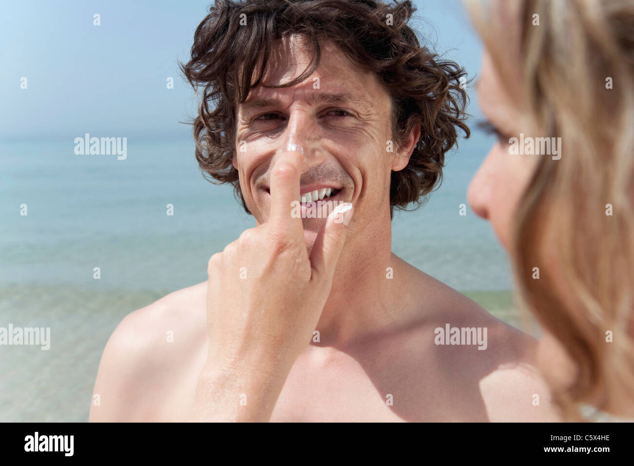 Spain, Mallorca, Woman applying suncream on man's nose - Stock Image