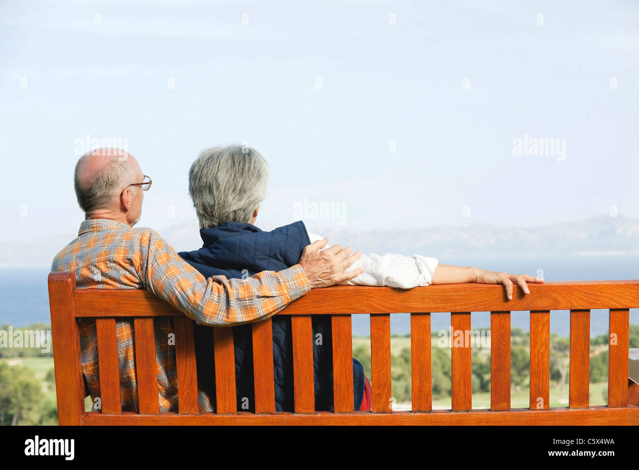 Spain, Mallorca, Senior couple sitting on bench, rear view - Stock Image