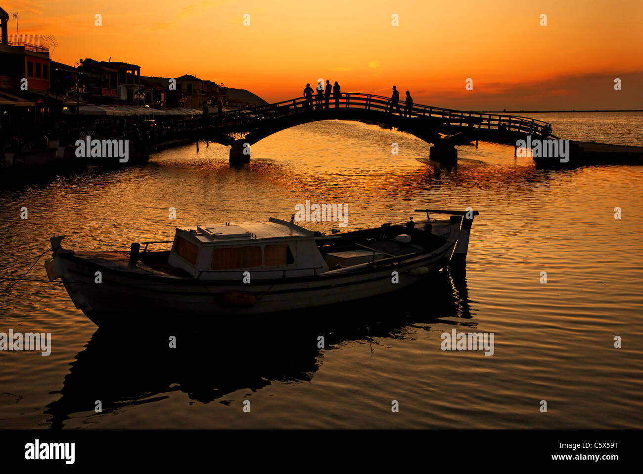 Sunset at Lefkas town, at the small marina for the fishing boats with the nice wooden bridge. Ionian islands, Greece. - Stock Image
