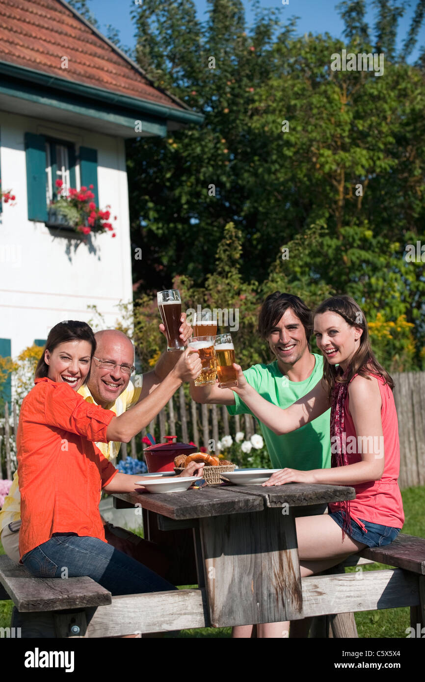 Germany, Bavaria, Friends drinking beer in the garden, clinking glasses - Stock Image
